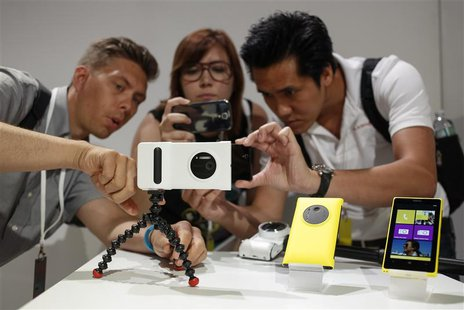 Guests at Nokia's unveiling of its new Lumia 1020 smartphone use the new phone's 41-megapixel camera with a grip in New York July 11, 2013.