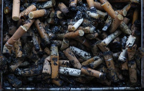 Used cigarette butts spill out of a full ashtray on the wall of a shopping centre in Warrington, northern England January 15, 2013. REUTERS/
