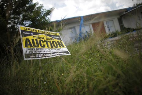 An auction sign for a property is seen at the front garden of a foreclosed house in Miami Gardens, Florida September 15, 2009. REUTERS/Carlo