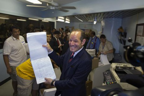 Former New York Governor Eliot Spitzer displays to the media, signatures which he delivered to the board of elections office, in New York Ju