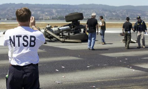 U.S. National Transportation Safety Board (NTSB) investigators attend to the scene of the Asiana Airlines Flight 214 crash site at San Franc