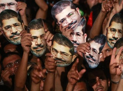 Members of the Muslim Brotherhood and supporters of deposed Egyptian President Mohamed Mursi hold up masks of him as they gather at the Raba