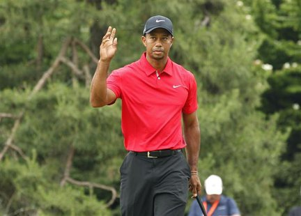 Tiger Woods of the U.S. reacts after putting on the first green during the final round of the 2013 U.S. Open golf championship at the Merion