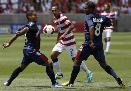 Cuba's Joel Colome (L) and Jaine Valencia defend against Edgar Castillo (C) of the U.S. during their CONCACAF Gold Cup soccer match in Salt