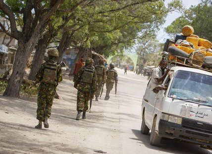 Soldiers, who are serving with the Kenyan Contingent of the African Union Mission in Somalia (AMISOM), patrol along a street as a commuter t