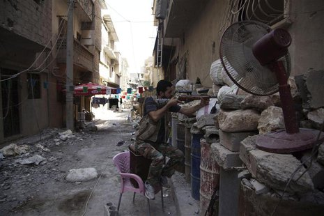 A Free Syrian Army fighter points his weapon as he takes up position behind sandbags in Deir al-Zor July 13, 2013. REUTERS/Khalil Ashawi