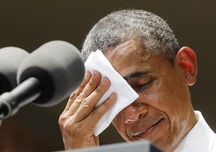 U.S. President Barack Obama pauses and wipes his face as he speaks about his vision to reduce carbon pollution while preparing the country f