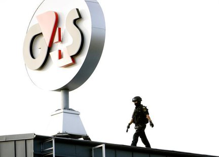 A police Swat team member walks on the roof of G4S cash depot in Vastberga, Stockholm September 23, 2009. REUTERS/Pontus Lundahl/Scanpix