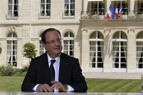 French President Francois Hollande speaks with journalists after a television interview in the garden of the Elysee Palace, following the tr