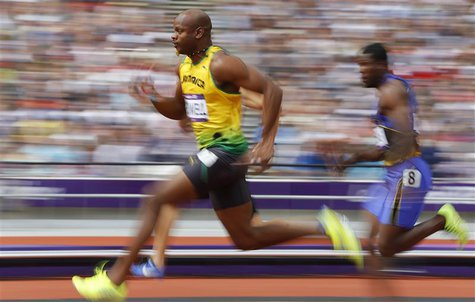 Asafa Powell of Jamaica runs on his way to winning his 100m heat round 1 during the London 2012 Olympic Games at the Olympic Stadium August