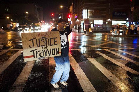 Will Reese holds a protest sign in response to the acquittal of George Zimmerman in the Trayvon Martin trial, in the Harlem neighborhood of