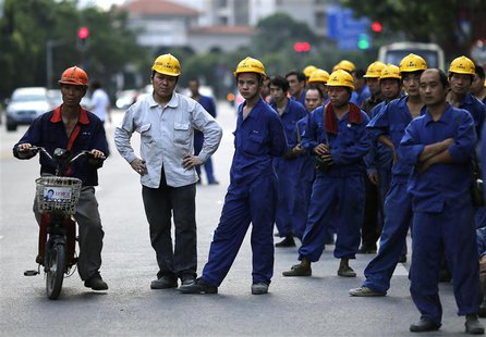 Construction workers wait for a bus after their workday at Pudong financial district in Shanghai July 8, 2013. China's resolve to revamp its