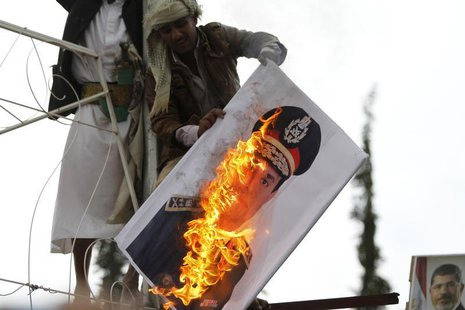 A pro-democracy protester burn an image of Lieutenant- General Abdel Fattah El Sisi, Egypt's Commanding General and Minister of Defense and