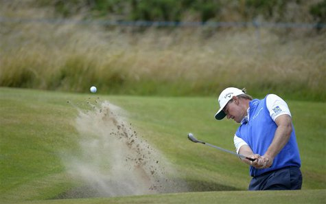 Ernie Els of South Africa hits out of a from a bunker on the third hole during a practice round ahead of the British Open golf championship