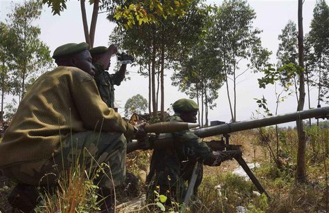 Congolese government army soldiers prepare their weapons at an attack position near Munigi, overlooking the front-line, where they are fight