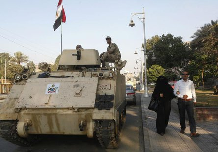 A couple walks past an Egyptian soldier keeping watch from atop a military vehicle in front of the presidential palace in Cairo July 14, 201