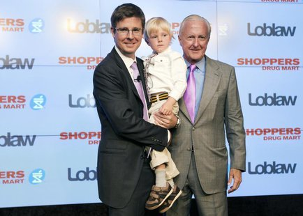 Executive chairman of Loblaw Companies Limited Galen G Weston (L) holds his son Graydon, as they pose with W. Galen Weston (R) in Toronto, J