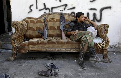 A Free Syrian Army fighter sits on a sofa in the old city of Aleppo, July 3, 2013. REUTERS/Muzaffar Salman