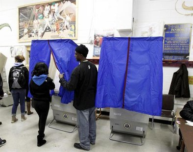 A poll worker assists a voter with the voting booth curtain before voting during the U.S. presidential election at the Penrose recreation ce