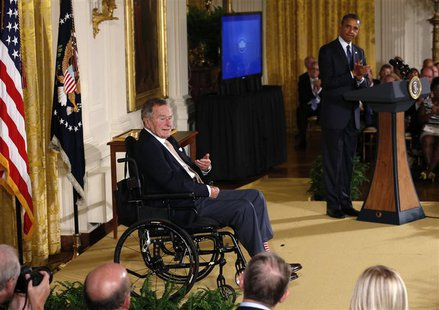 U.S. President Barack Obama applauds former President George H. W. Bush (L) during an event to honor the winner of the 5,000th Daily Point o