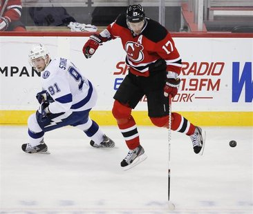 New Jersey Devils right wing Ilya Kovalchuk (17) leaps over the puck in front of Tampa Bay Lightning center Steven Stamkos (91) in the third