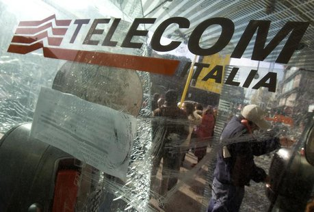 A man uses a Telecom Italia phone booth at a bus stop in Rome December 3, 2008. REUTERS/Chris Helgren