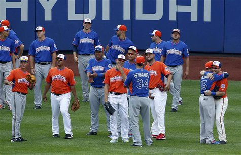 Major League All-Stars greet one another in the outfield during practice before the Major League Baseball All-Star Game Home Run Derby in Ne