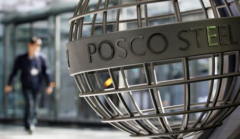 An employee of POSCO walks next to a sculpture with POSCO's logo at the company's headquarters in Seoul October 21, 2011. REUTERS/Jo Yong-Ha