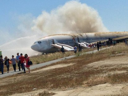 Passengers evacuate the Asiana Airlines Boeing 777 aircraft after a crash landing at San Francisco International Airport in California July
