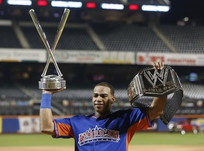 American League batter Yoenis Cespedes, of the Oakland A's, holds up the Home Run trophy and a belt after winning the Major League Baseball