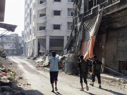 Members of the Free Syrian Army walk along a damaged street filled with debris in the besieged area of Homs July 13, 2013. REUTERS/Yazan Hom