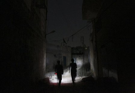 Free Syrian Army fighters move along a street at night in Aleppo's Karm al-Jabal district July 15, 2013. Picture taken July 15, 2013. REUTER
