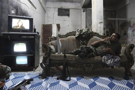 A Free Syrian Army fighter rests on a sofa as he watches television and surveillance monitors inside a room in Aleppo's Karm al-Jabal distri