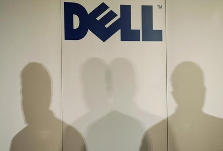 Shadows of Michael Dell, chairman of the board and chief executive officer of Dell, are cast under the company logo as he speaks during a pr