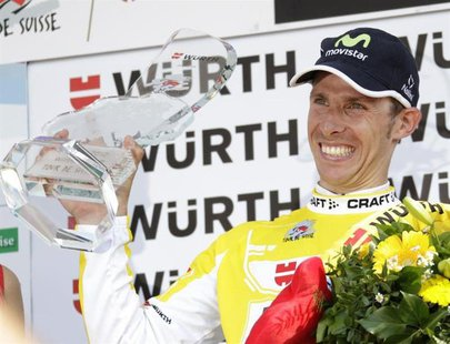 Movistar rider Rui Costa of Portugal celebrates with the winner's trophy on the podium after the ninth and final stage of the Tour de Suisse