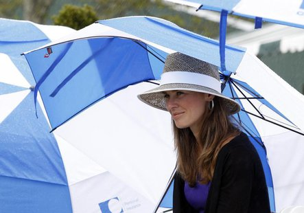 Martina Hingis takes shelter under an umbrella as rain falls during the Tennis Hall of Fame induction ceremony in Newport, Rhode Island July