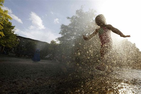 A girl cools off in the water from a playground sprinkler in the Brooklyn borough of New York July 15, 2013. REUTERS/Brendan McDermid