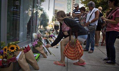 People gather at a small memorial to Canadian actor Cory Monteith outside the Fairmont Pacific Rim Hotel in Vancouver, British Columbia July