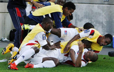 The Cuba team piles onto Jeniel Molina (bottom R) after he scored against Belize during their CONCACAF Gold Cup soccer match in Hartford, Co
