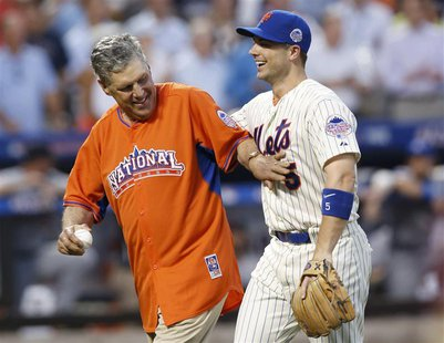 Former New York Mets pitcher Tom Seaver (L) is greeted by the Mets' David Wright after throwing out the ceremonial first pitch ahead of Majo