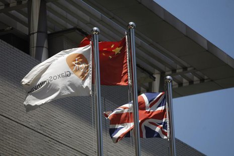A flag (L) bearing the logo of GlaxoSmithKline (GSK) flutters next to a Chinese national flag (C) and a Union Flag (R), outside a GlaxoSmith