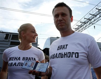 Anti-corruption blogger Alexei Navalny holds his Moscow mayor candidate registration certificate as his wife Yulia looks on before leaving f