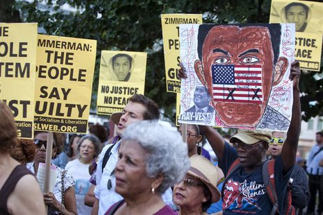 People attend a vigil for slain youth Trayvon Martin, as well as to protest the acquittal of George Zimmerman for the shooting death of Mart
