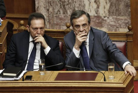 Greece's Prime Minister Antonis Samaras (R) and Finance Minister Yannis Stournaras attend a parliament session during a vote on a series of