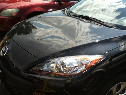 vandals smashed the hood of this Mazda 3