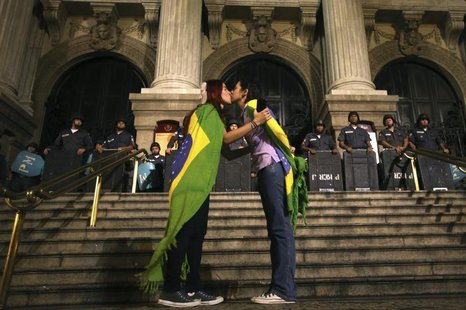 Two demonstrators kiss each other in front of police officers during a protest in central Rio de Janeiro June 27, 2013. REUTERS/Pilar Olivar