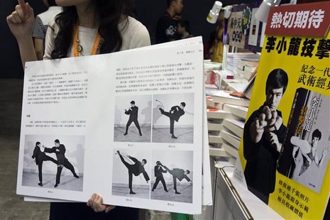 "A shopkeeper introduces a latest Chinese edition of ""Bruce Lee's Fighting Method"" by the late Kung Fu legend Bruce Lee on the first day of t"