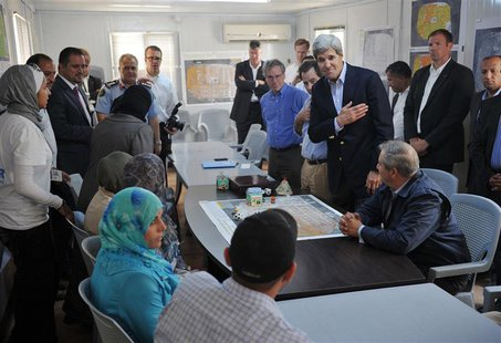 U.S. Secretary of State John Kerry (2nd R) greets a group of Syrian refugees during a joint meeting with Jordanian Foreign Minister Nasser J