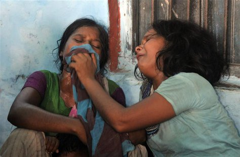 Women mourn the death of their children who died after consuming contaminated meals given to children at a school on Tuesday at Chapra in th