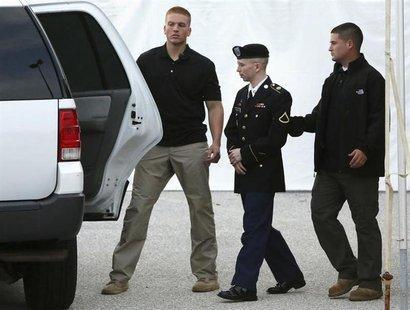 U.S. Army Private First Class Bradley Manning (C) is escorted out after a day of testimony at his court martial trial at Fort Meade, Marylan